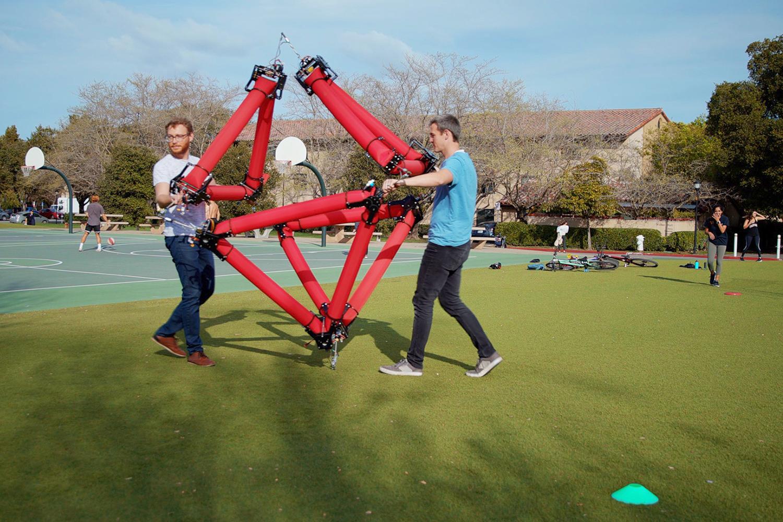 robô flexível sendo carregado por dois estudantes