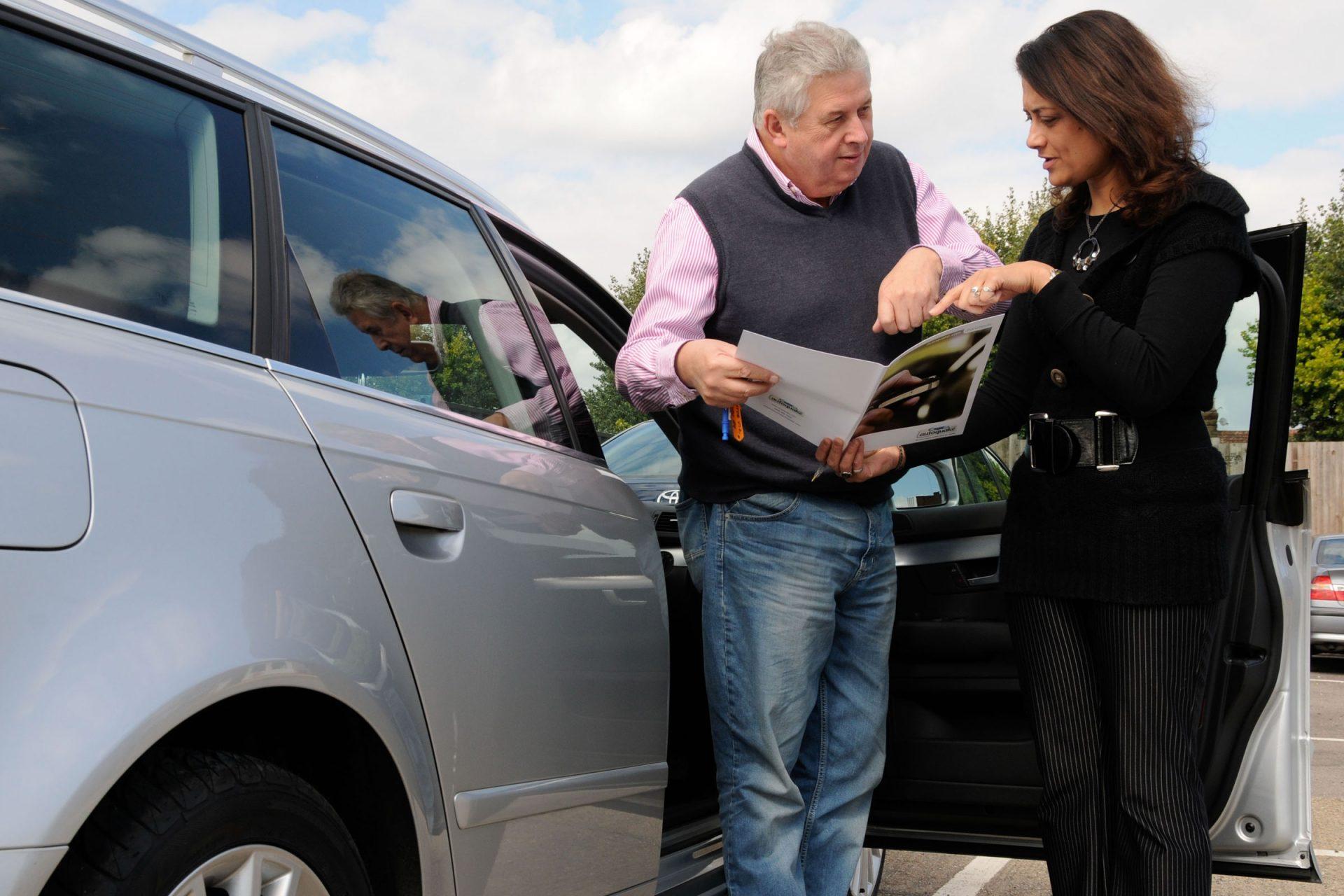homem e mulher conversando ao lado de automóvel
