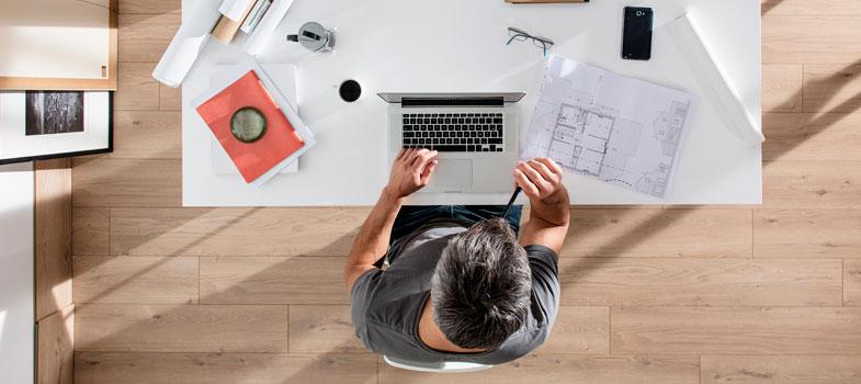 homem sentado a escrivaninha digitando no computador fazendo trabalho remoto