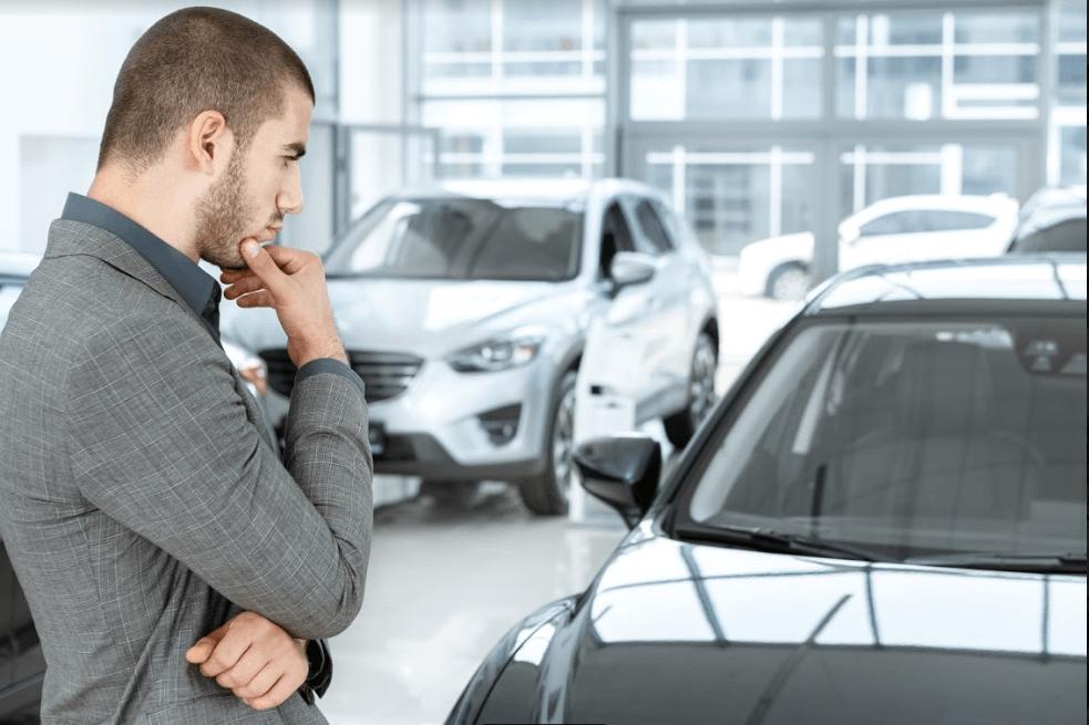homem olhando para automóvel em dúvida