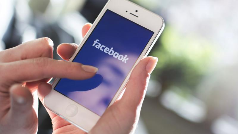 mão segurando celular e usando facebook