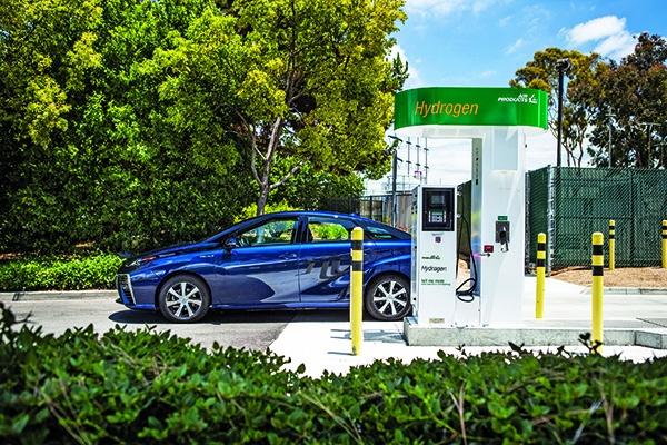 Carros  parado ao lado de posto de abastecimento de hidrogênio