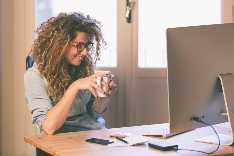 mulher em mesa com computador sorrindo
