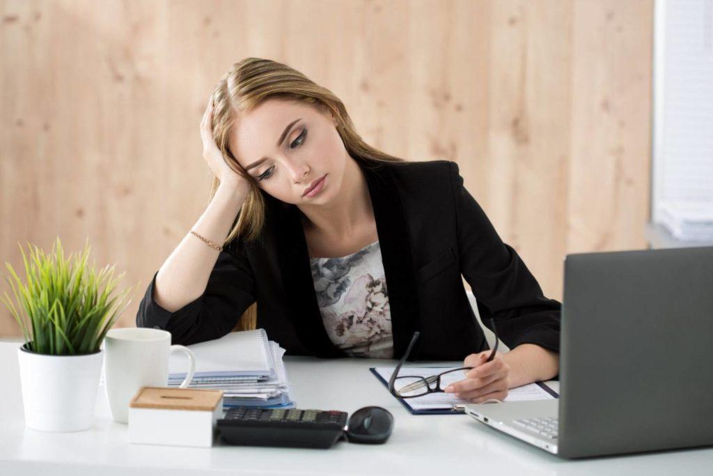 mulher olhando para o a mesa e usando computador entediada