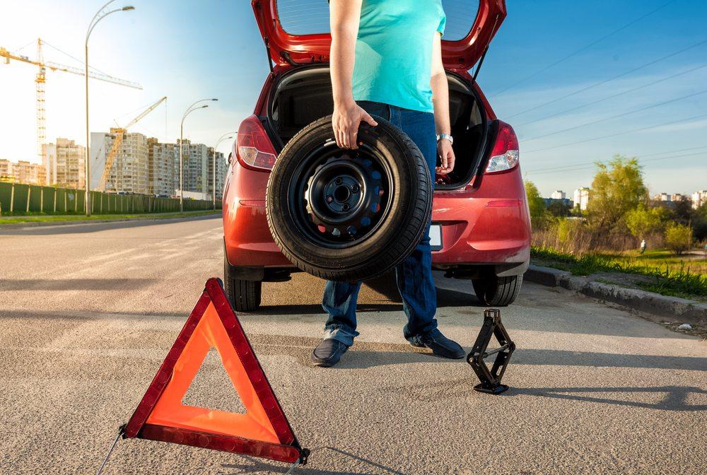 homem parado ao lado de carro segurando pneu nas mãos e a frente de triângulo