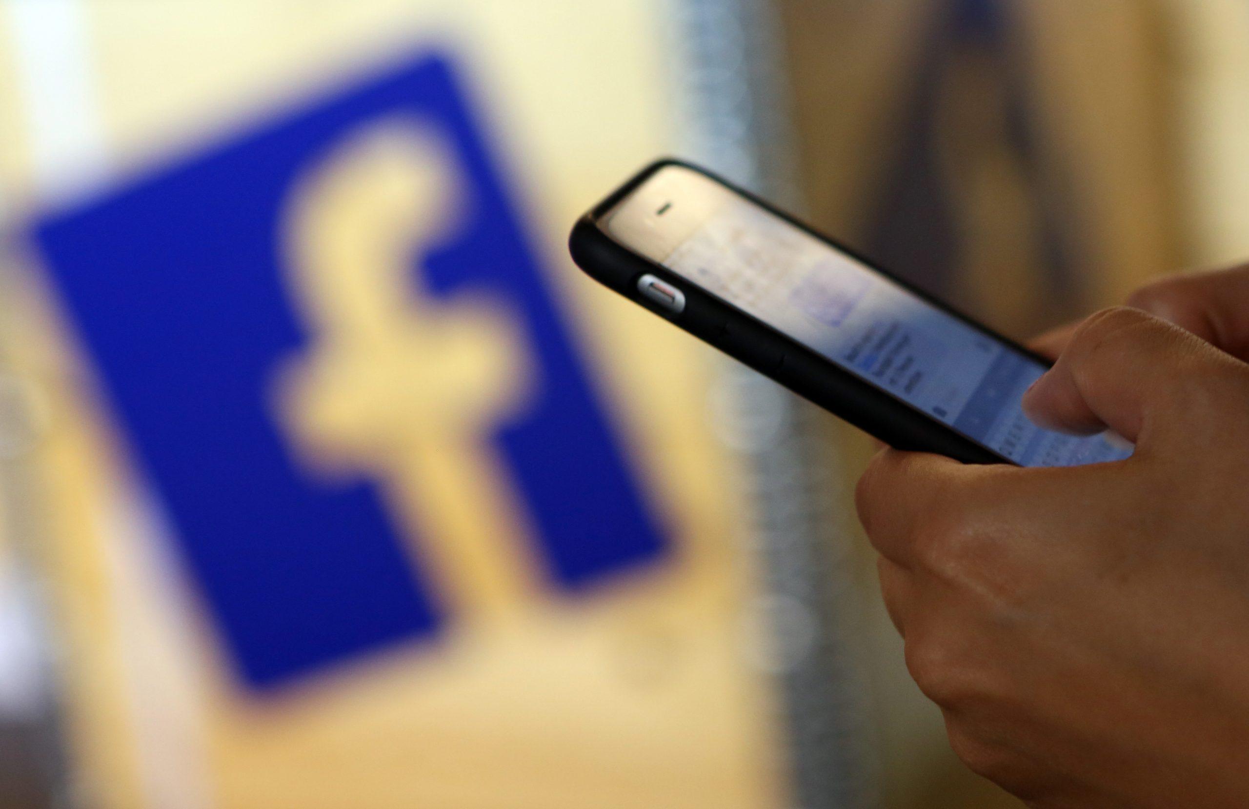 pessoa com celular na mão e logo do Facebook ao fundo