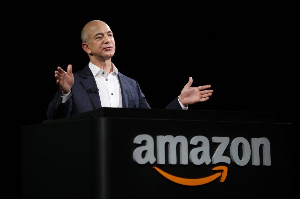 Jeff Bezos em pé atrás de estande da Amazon