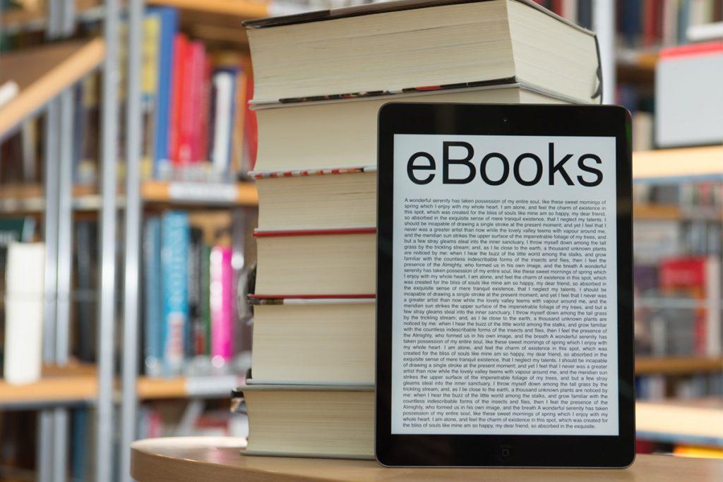 livros empilhados com ebook a frente
