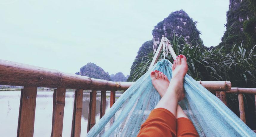 mulher deitada na rede com pés aparecendo