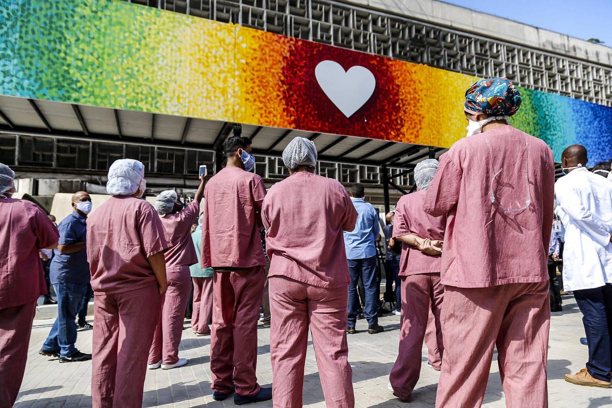 Colaboradores do hospital em frente à fachada com símbolo de coração.