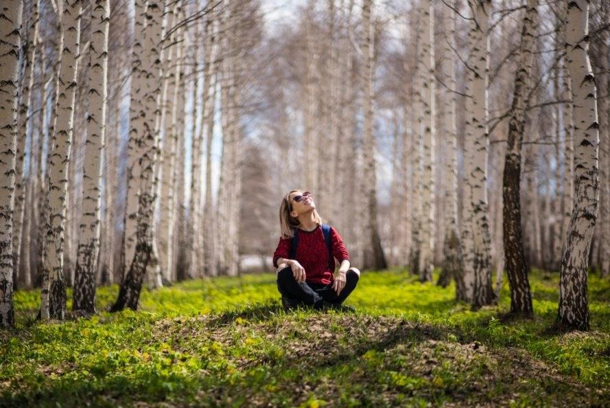 mulher sentada na floresta olhando para o nada em momentos ociosos