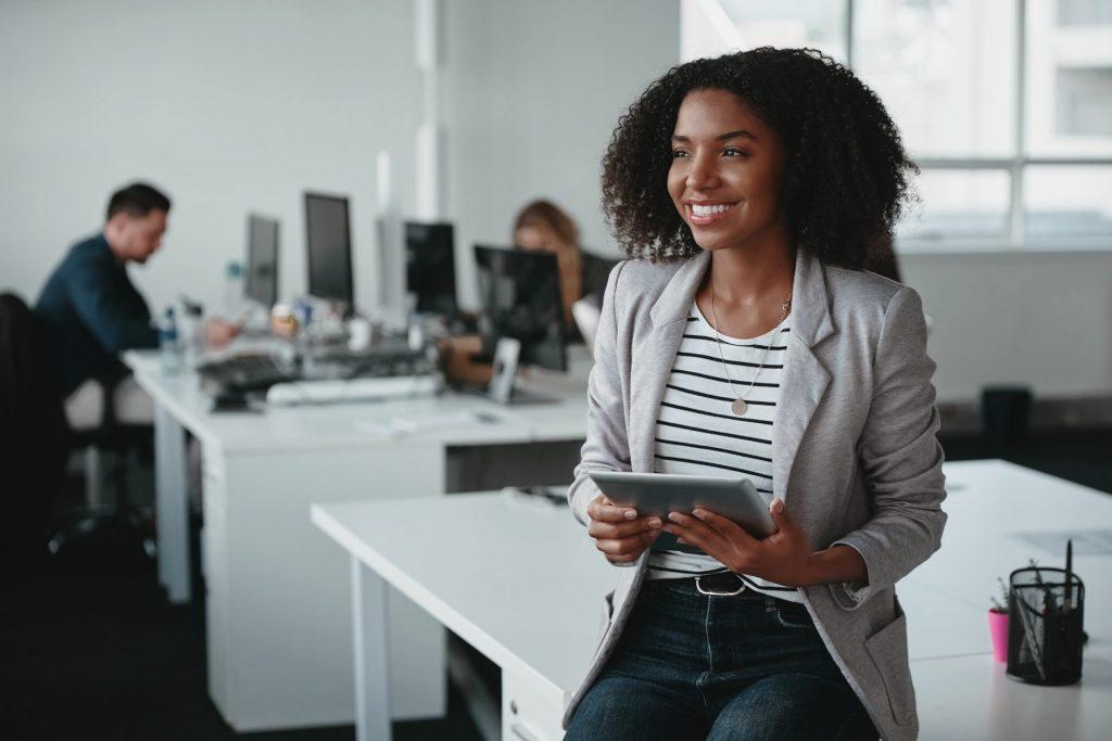 Imagem de mulher negra em sala de escritório representando mais mulheres na engenharia em escritórios e salas de aula.