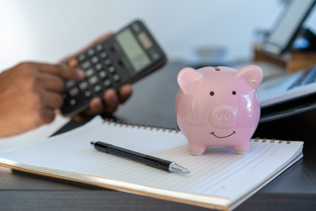 mão segurando calculadora e fazendo conta financeiras