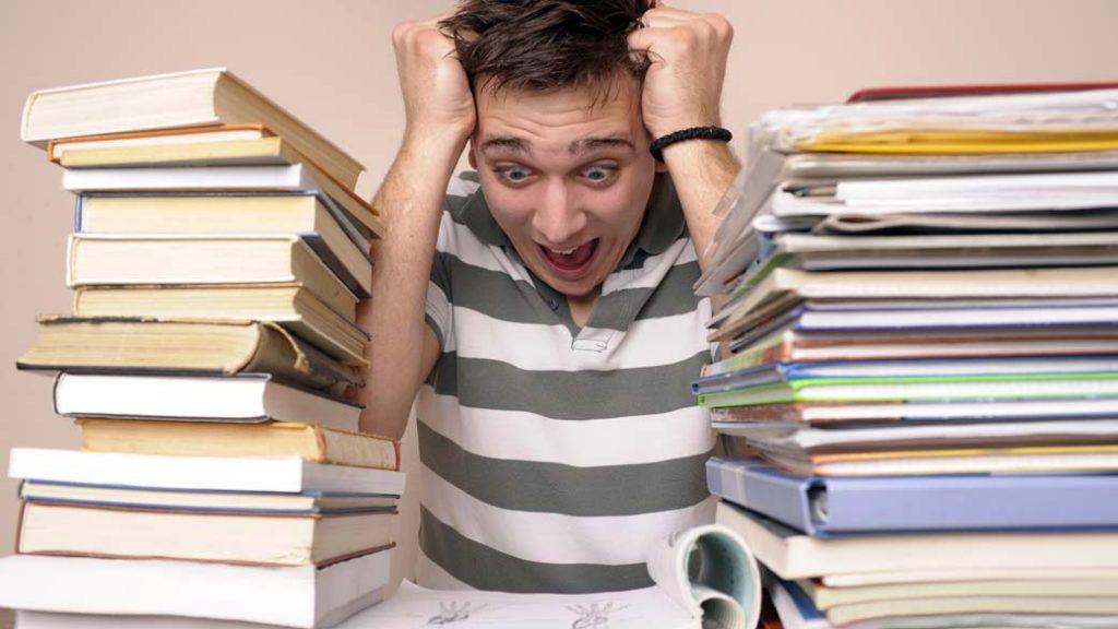 estudante surtando entre duas pilhas de livros