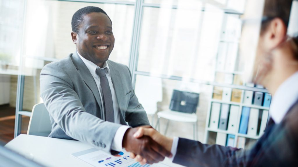 homem negro e homem branco apertando as mãos em entrevista de emprego
