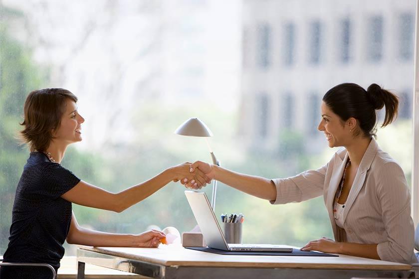 duas mulheres apertando as mãos em entrevista de emprego