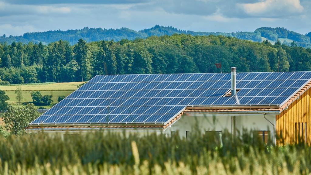 Fotografia de uma casa no campo que possui painéis fotovoltaicos em seu telhado