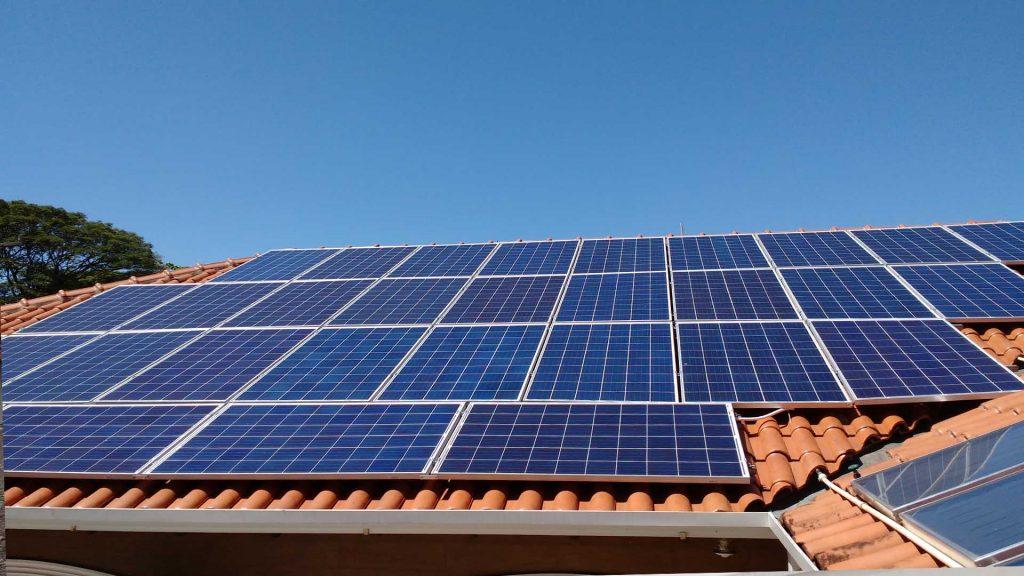 Fotografia de um sistema solar fotovoltaico instalado sob o telhado de uma residência