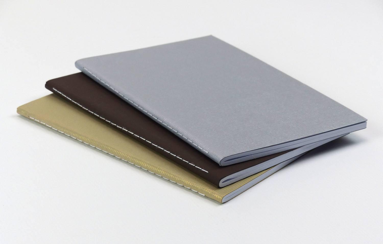três cadernetas em um fundo branco