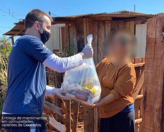 Registro de colaborador de empresa construtora entregando cesta básica em ação social.