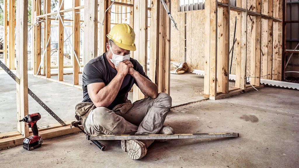 Homem com máscara e capacete em canteiro de obras sentado.