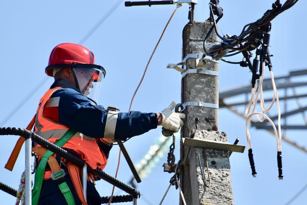 eletricista em poste arrumando fiação