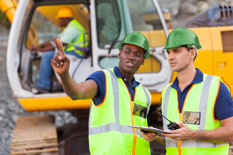 Dois engenheiros em campo em pátio industrial utilizando EPI's.