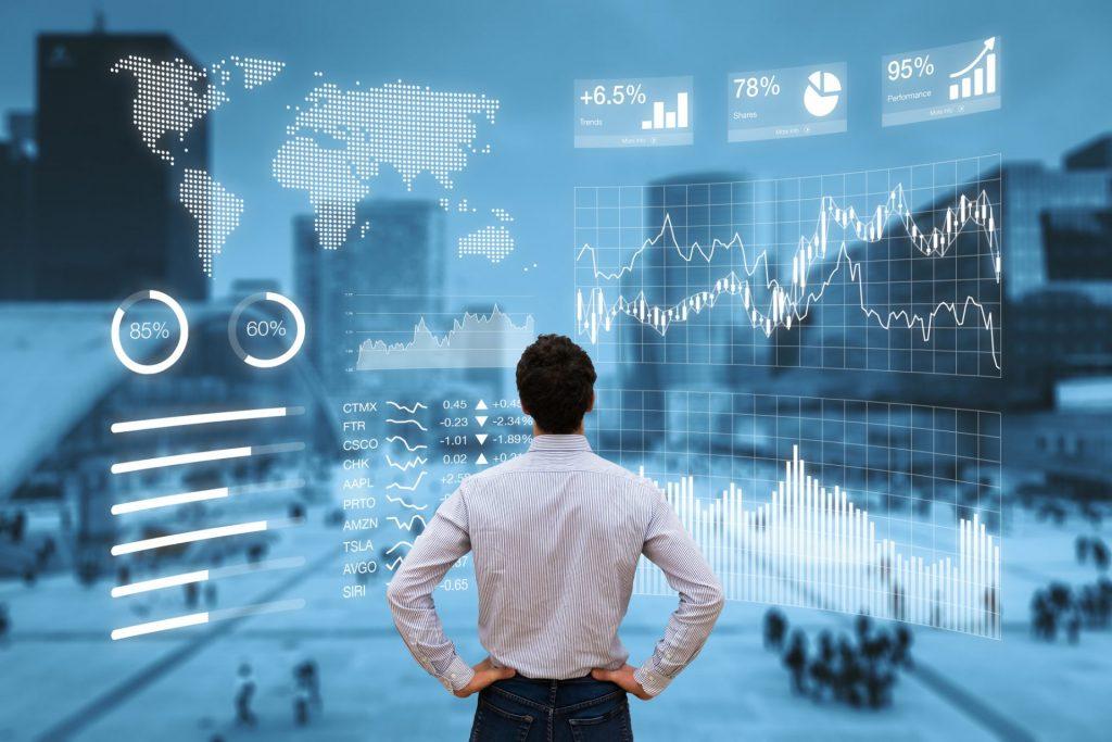 Engenheiro de costas olhando para painel digital com gráficos de análise.