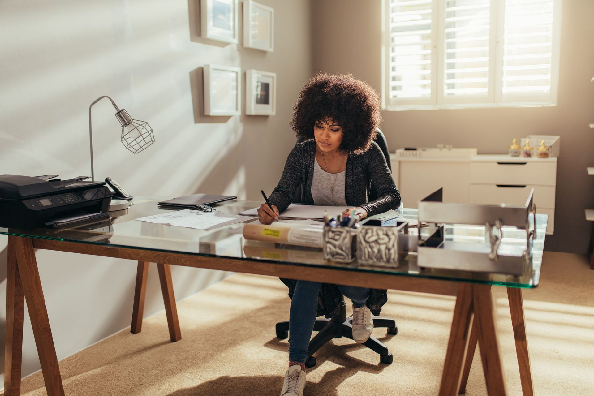 mulher sentada em mesa usando computador em home office