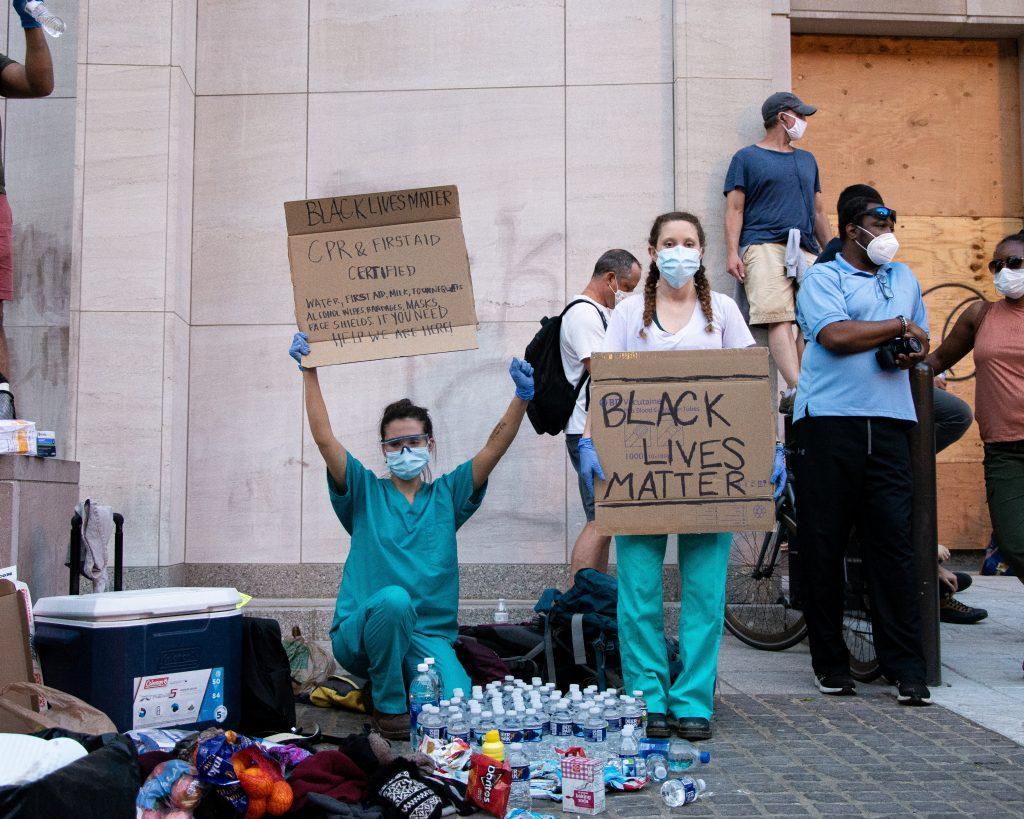 Pessoas usando máscaras em manifestação de Black Lives Matter durante pandemia de covid-19.