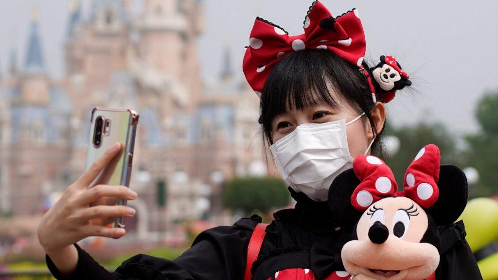 mulher com minnie tirando selfie de máscara