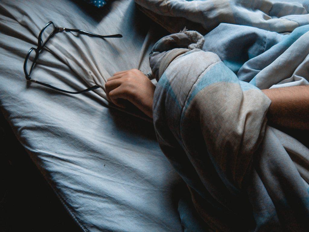 Dormir - imagem pessoa dormindo com as mãos próximas aos óculos