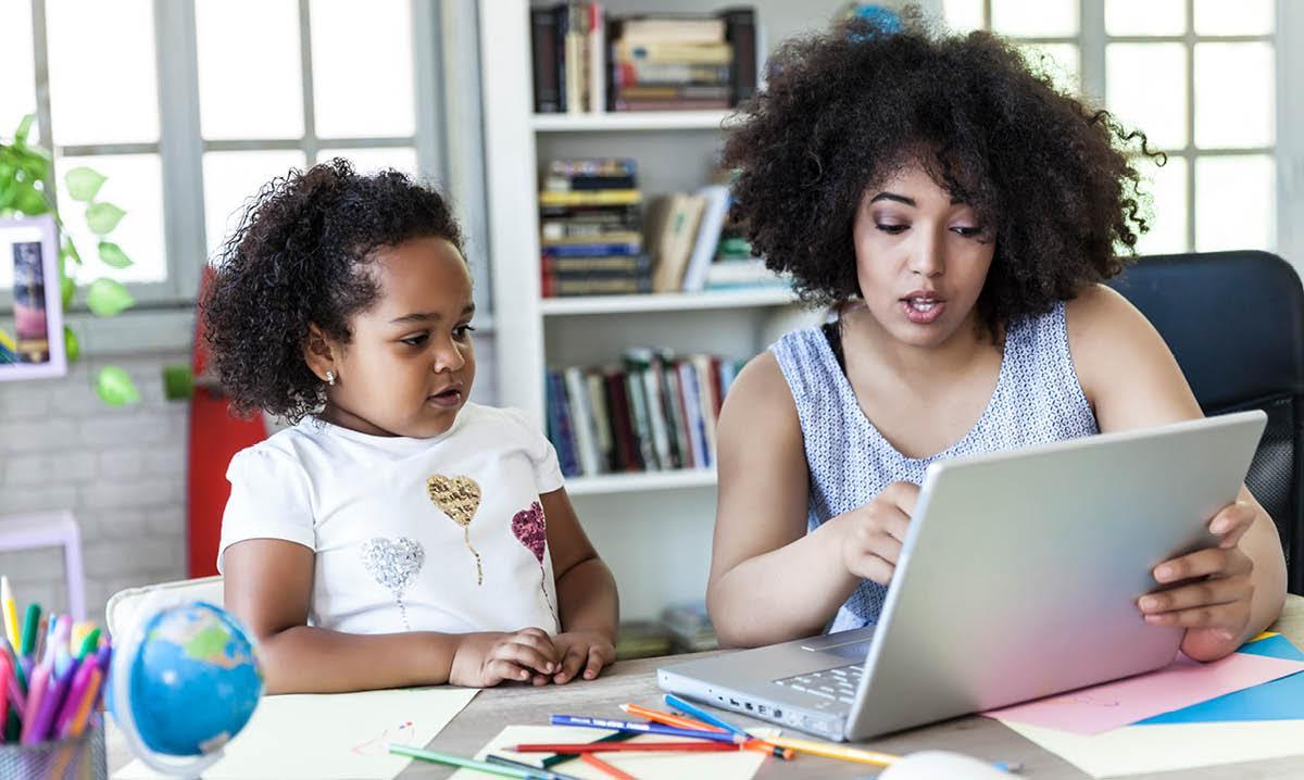 mulher ensinando criança em casa, ambas olhando para o computador