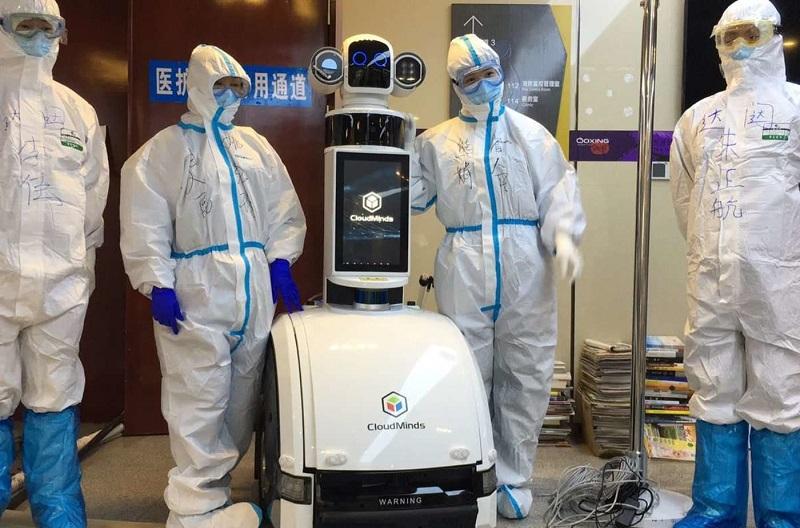 quatro homens com roupa de segurança e um robô epidemia coronavirus