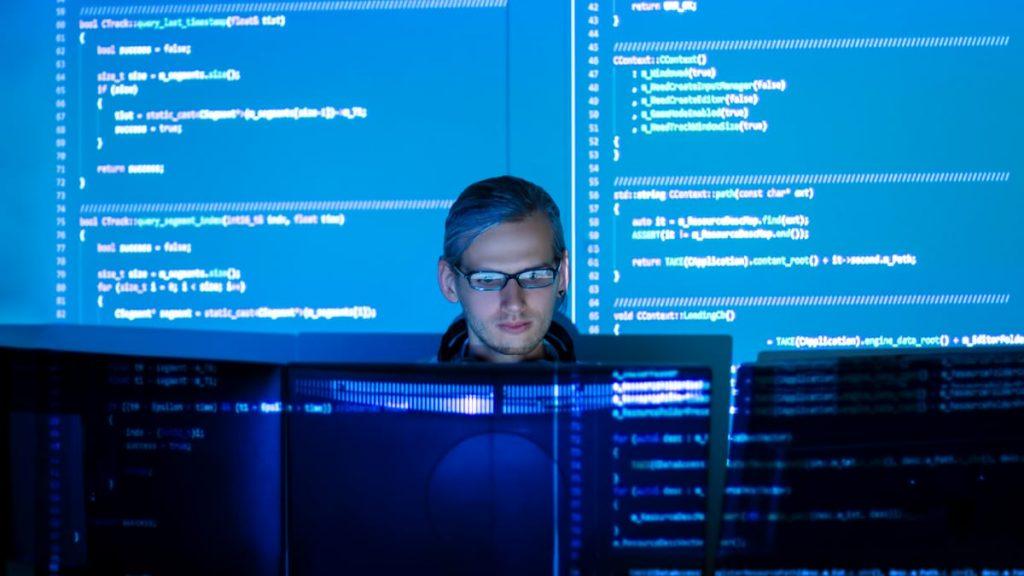 Profissional de tecnologia da informação utilizando computadores no trabalho.