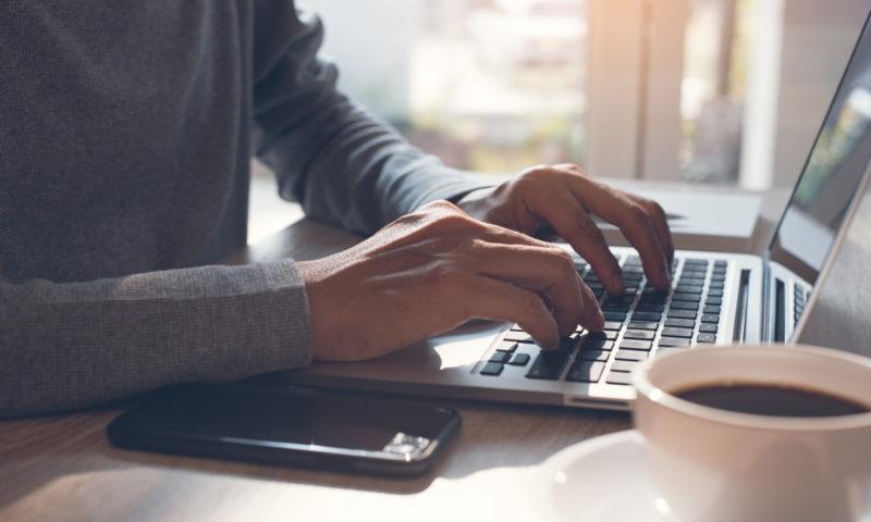 pessoa trabalhando em casa na frente do computador junto ao celular e um café