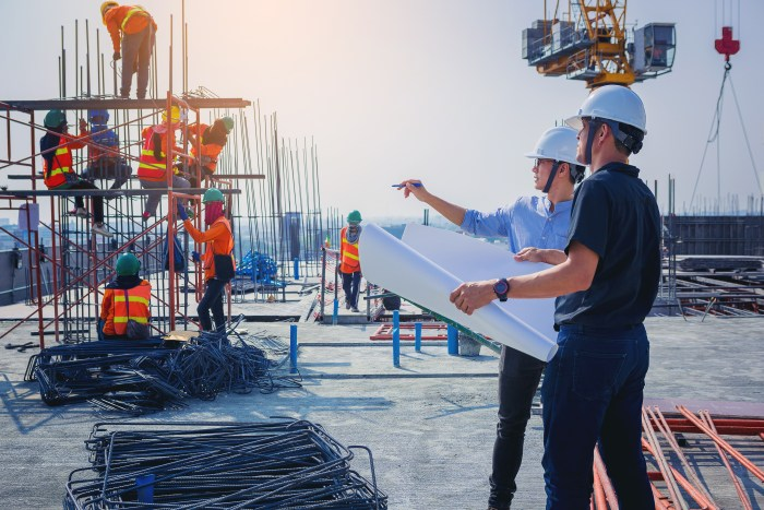 A foto mostra dois engenheiros civis em uma obra, conversando acerca de algum assunto relacionado ao trabalho.