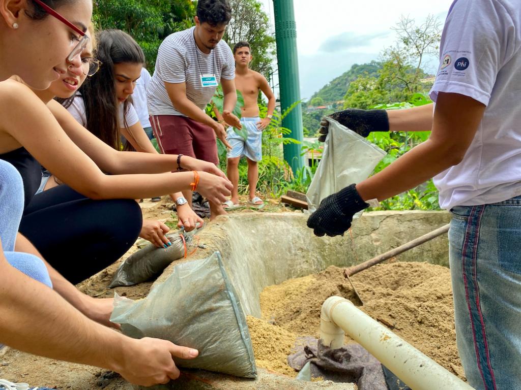 Terra, concreto e canos PVC sendo manipulados por pessoas, para a construção de uma estrutura de saneamento ecológico representando engenharia popular