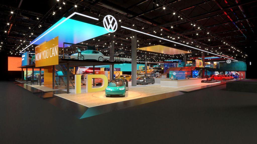 """Showroom da Volkswagen com a apresentação do ID.3. O piso em madeira e diversos veículos dispostos ao longo do espaço. É possível ler a frase """"Now you can"""" em um dos painéis"""