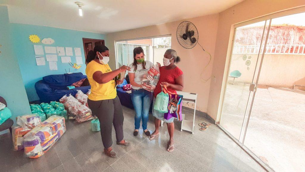 jovens entregando cesta básic engenheiros sem fronteiras