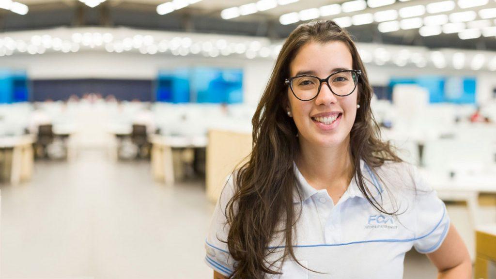 Juliana Coelho no setor de desenvolvimento de manufaturas com o fundo do setor desfocado