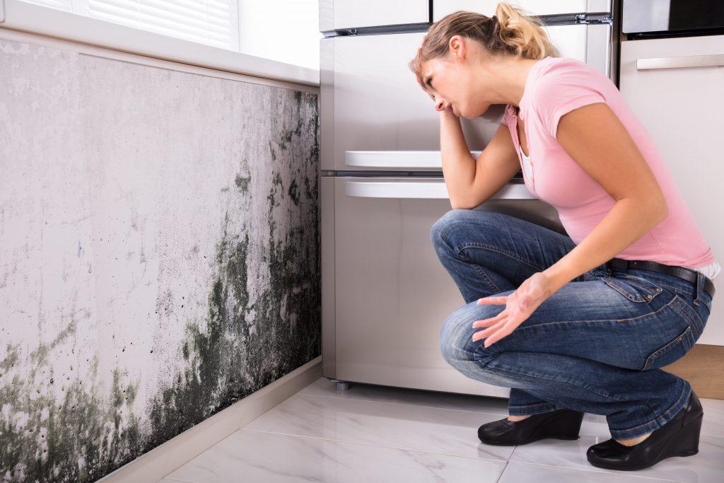 Mulher preocupada com infiltração causada por ausência de impermeabilização