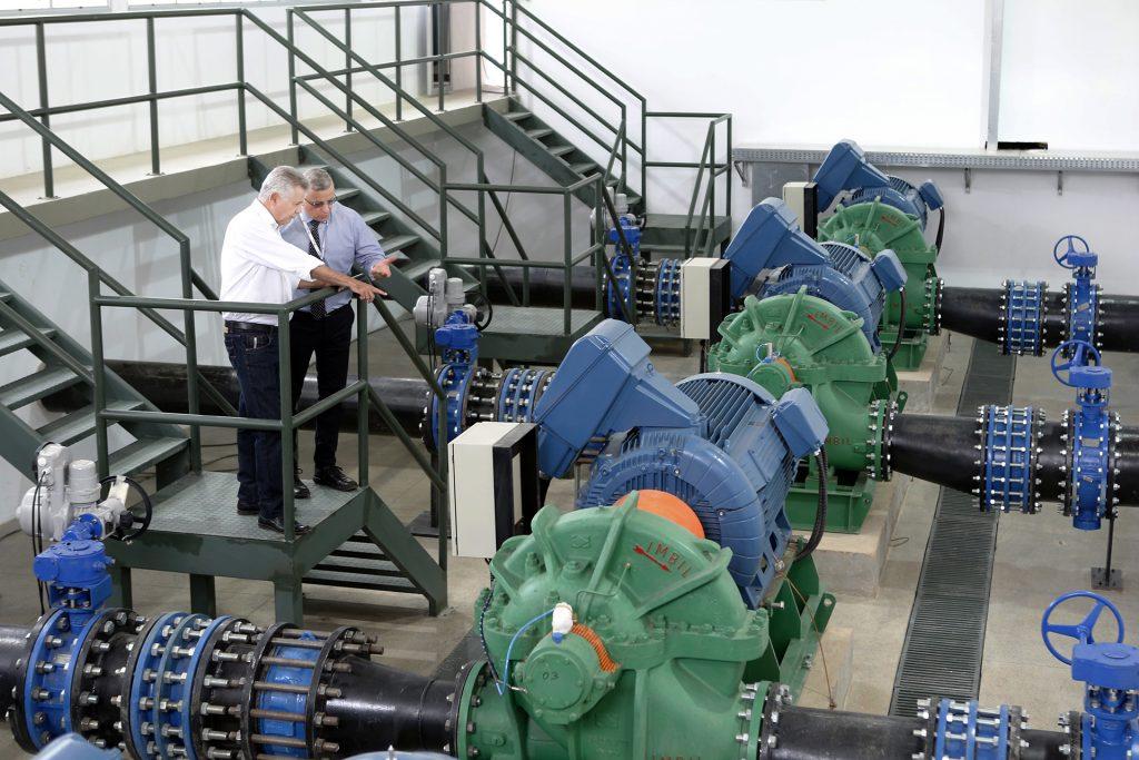 Dois engenheiros analisando sala de máquinas de bombeamento de água potável.
