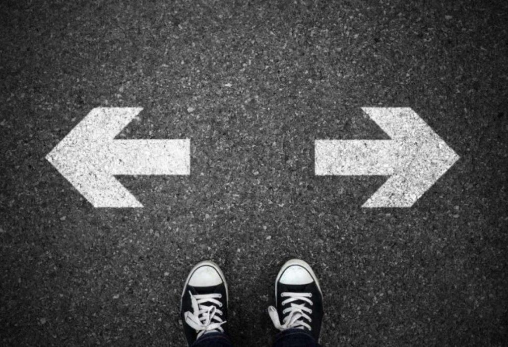 Calçados parados em frente a duas sextas, uma indicando para direita e outra para a esquerda, simbolizando uma tomada de decisão.