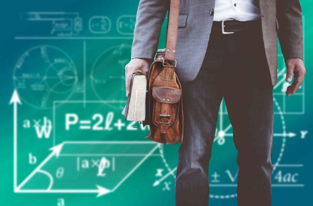 Homem de bolsa marrom segurando um livro em frente ao fundo com cálculos matemáticos representando mestrado