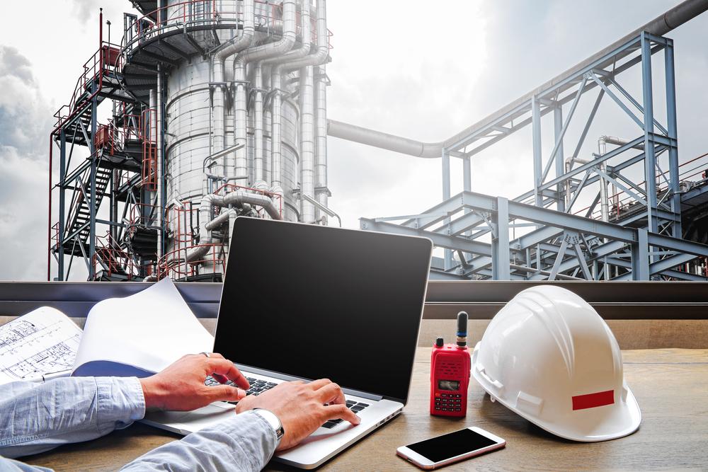 Homem utilizando um notebook ao lado de um capacete branco próximo a uma instalação industrial