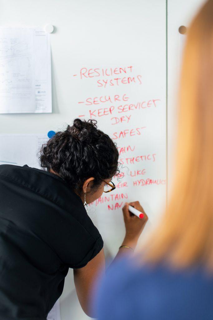 mulher escrevendo em quadro ilustrando processo de comunicação