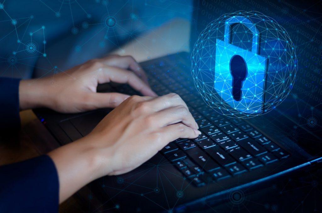 Mãos de uma pessoa utilizando laptop. Em destaque aparece um cadeado, simbolizando a segurança de dados.