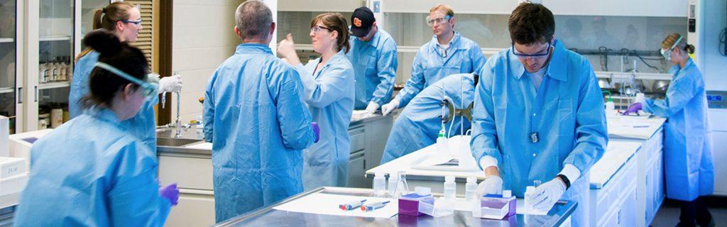 Equipe de engenheiros nucleares de uniforme azul utilizando EPI's no laboratório de análises