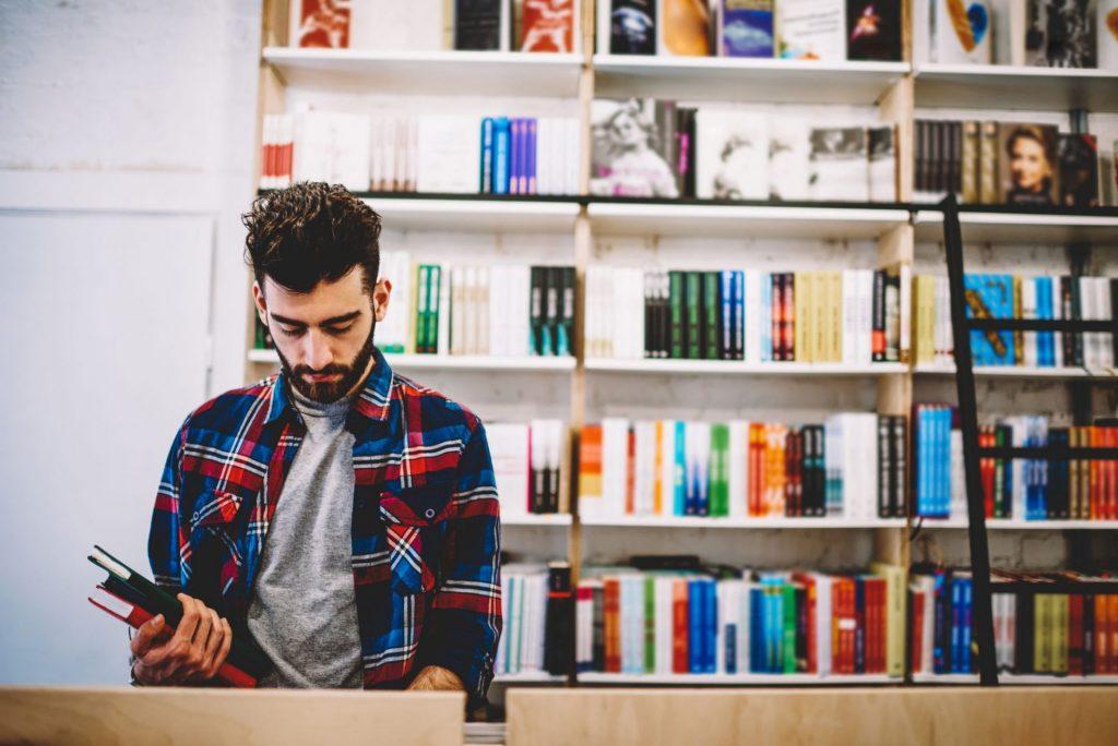Homem de camisa quadriculada estudando em frente a uma prateleira de livros